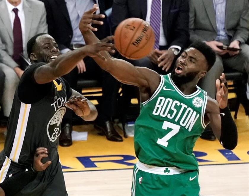 Golden State Warriors forward Draymond Green (L) and Boston Celtics guard Jaylen Brown (R) reach out for a rebound during the second half of the NBA basketball game between the Boston Celtics and the Golden State Warriors at Oracle Arena in Oakland, California, USA. EFE