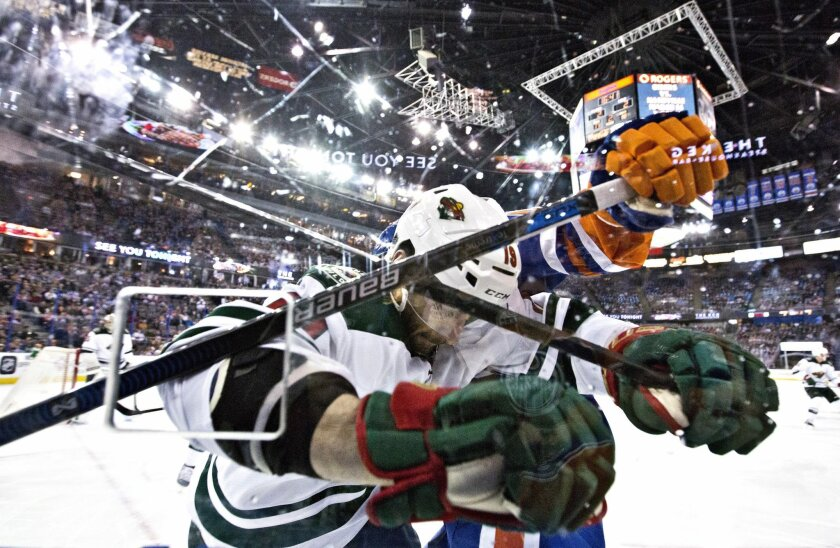 Minnesota Wild's Jarret Stoll (19) and Edmonton Oilers' Teddy Purcell battle in the corner during the second period of an NHL hockey game Thursday, Feb. 18, 2016, in Edmonton, Alberta. (Jason Franson/The Canadian Press via AP)