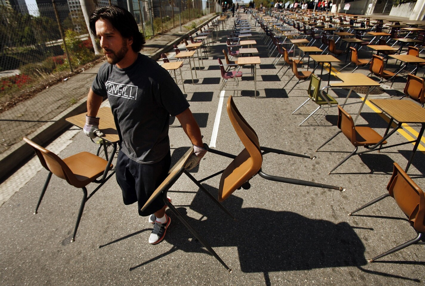 Ben Weischedel with the L.A. Rugby Club in support for United Way starts to load 375 school desks that were blocking Beaudry Avenue in front of L.A. Unified headquarters Tuesday. The 375 desks represent the number of students who drop out of school every week of a school year.