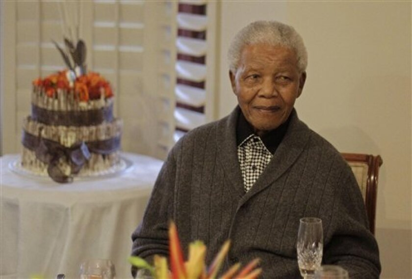 "FILE - In this Wednesday, July 18, 2012 file photo, former South African President Nelson Mandela as he celebrates his 94th birthday with family in Qunu, South Africa.  A South African official says Mandela is breathing ""without difficulty"" after having a procedure to clear fluid in his lung area t"
