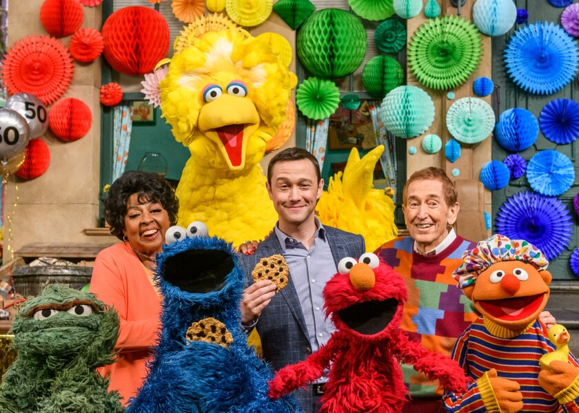 "A scene from ""Sesame Street's"" 50th anniversary special featuring Loretta Long, left, host Joseph Gordon-Levitt and Bob McGrath."