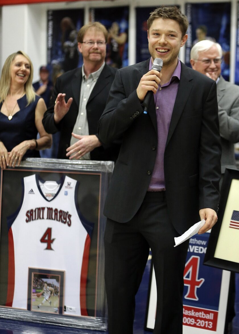 Cleveland Cavaliers' Matthew Dellavedova speaks during a jersey retirement ceremony before an NCAA college basketball game between Saint Mary's and BYU, Saturday, Feb. 15, 2014, in Moraga, Calif. Dellavedova played for Saint Mary's from 2009-2013. Dellavedova's parents, Mark and Leanne, background left, look on. (AP Photo/Ben Margot)
