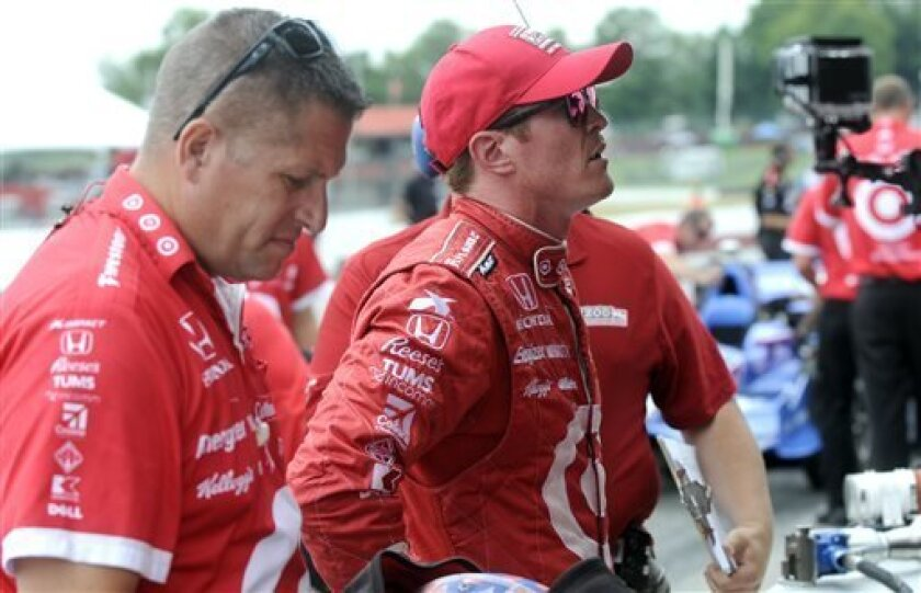 Scott Dixon, of New Zealand, watches on pit road talking with his crew during practice for the IndyCar auto race at Mid-Ohio Sports Car Course in Lexington, Ohio, Friday, Aug. 2, 2013. (AP Photo/Tom E. Puskar)