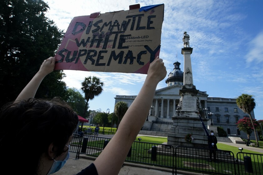 A demonstrator protests in front of a civil war statue at the State House on Friday, July 10, 2020, in Columbia, S.C. Demonstrators on both sides gathered for the five year anniversary after the Confederate battle flag was removed from the State House grounds after a two-thirds vote by the Legislature. (AP Photo/Chris Carlson)