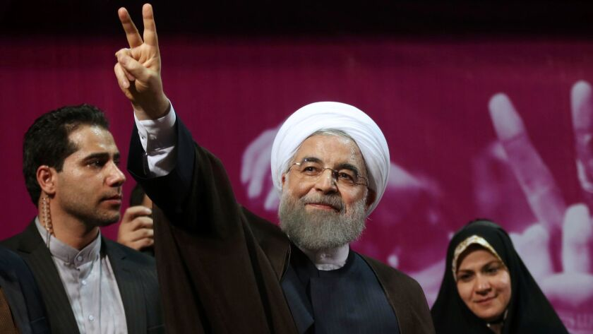 Iranian President Hassan Rouhani flashes a victory sign at the conclusion of his speech in a campaig