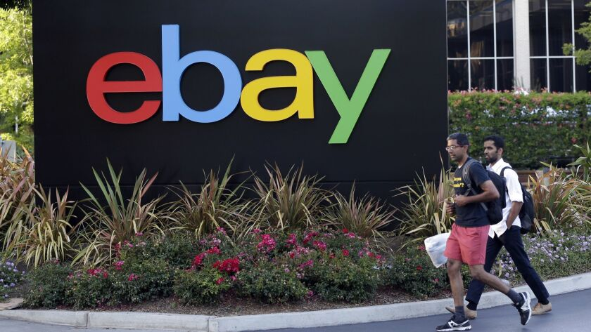 In this June 5, 2014 photo, people walk in front of an eBay Inc. sign at the company's headquarters