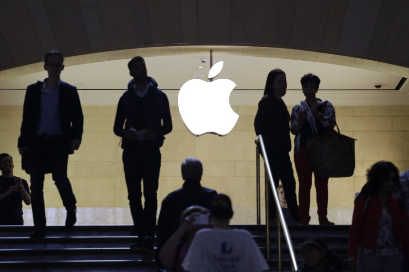 Customers and staff in the entrance to the Apple store in New York's Grand Central Terminal. Apple has hired a former Chrysler manufacturing executive and other auto experts as it researches the auto market.