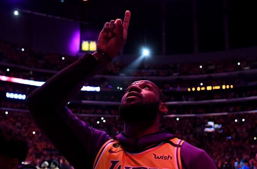 LeBron James points to the sky during a moment to honor Kobe Bryant in the Lakers' first game after the legend's death.