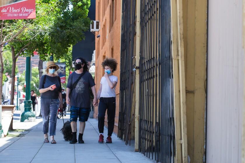 Masked pedestrians walk their dog in Little Italy on July 3, 2020.
