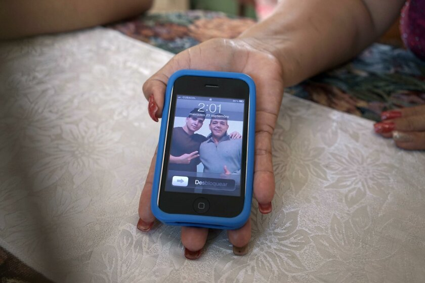 In this Sept. 23, 2015 photo, Olea Lastre, a hairdresser, shows a photo of her husband Antonio Cardenas with her son Jose Fuentes Lastre, taken in the U.S. after they survived 10 days at sea on a raft in the Florida Straits, on her cell phone in Camaguey, Cuba. The men fled last year and now live i