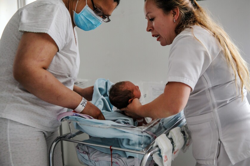 BOGOTA, D.C. -- FRIDAY, MAY 3, 2019: Belys Torrealba Tovar, 24, reaches for her newborn, Angel, at t