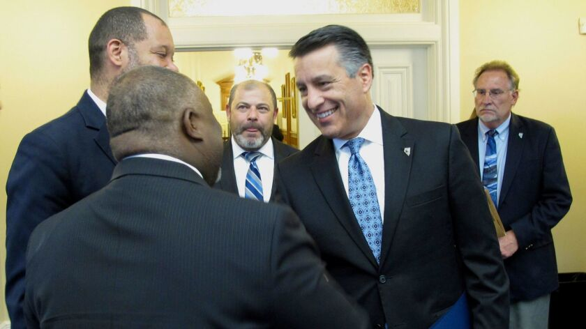 Nevada Republican Gov. Brian Sandoval shakes hands with Democratic Assembly Speaker Jason Frierson,
