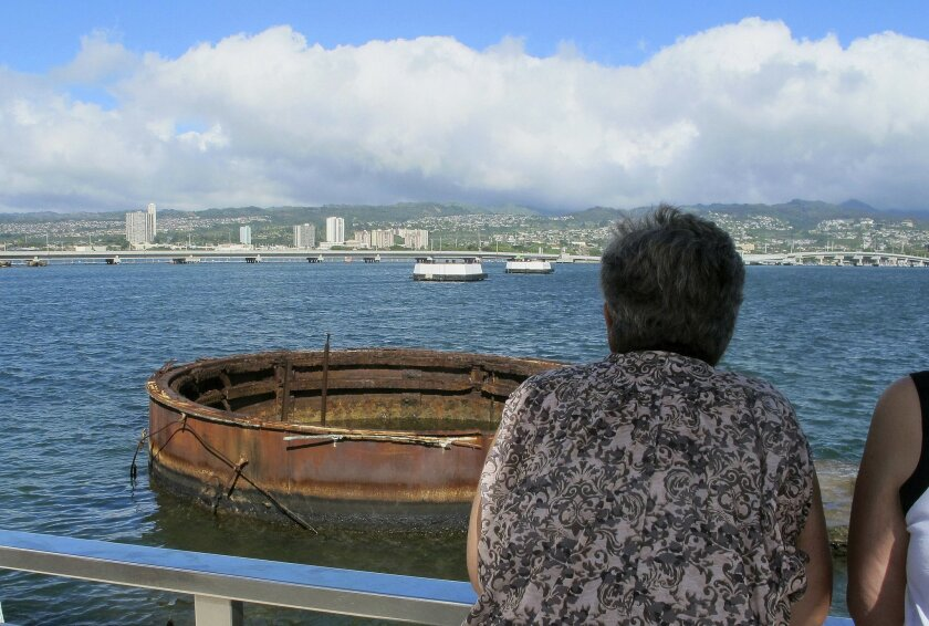 This Nov. 21, 2014 photo shows visitors looking out at the sunken USS Arizona from a memorial atop the rusting battleship in Pearl Harbor, Hawaii. The USS Arizona is one of the nation's most hallowed sites, an underwater grave for more than 900 sailors and Marines killed when Japan bombed Pearl Har