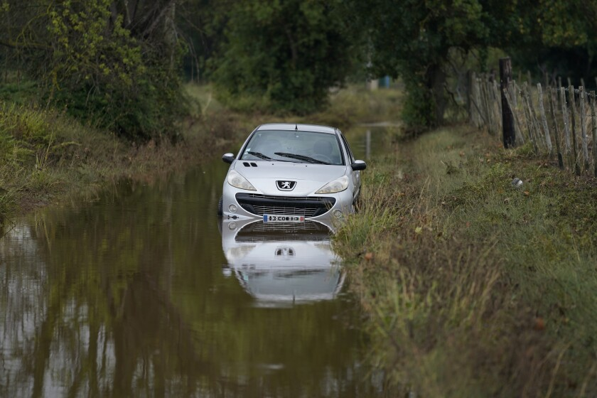 A car is seen flooded in Bernis, southern France,Wednesday, Sept. 15, 2021 in Paris. Emergency workers rescued or evacuated hundreds of people in southern France as flash flooding abruptly turned roads and fields into rivers and lakes. As new heavy rainfall threatened the area Wednesday, the emergency service for the Gard region said rescuers were searching for at least one person reported missing after the Tuesday evening flood. (AP Photo/Daniel Cole)