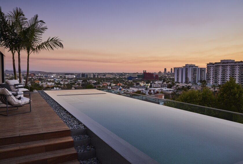 This photo shows a pool atop a condo highrise with city views beyond.