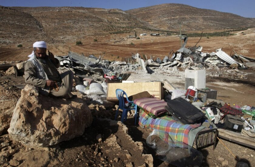 A Palestinian man sits by the remains of his house destroyed last month in Aqraba village near the West Bank city of Nablus. The Israeli military said it demolished four structures that had been built illegally in the village.