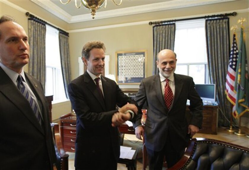 Treasury Secretary Timothy Geithner, center, and Federal Reserve Chairman Ben Bernanke, right, gather in Geithner's office just before meeting with reporters to discuss ongoing repairs to the economy, at the Treasury in Washington, Thursday, May 7, 2009. They are joined by Comptroller of the Currency John Dugan at left. (AP Photo/J. Scott Applewhite)
