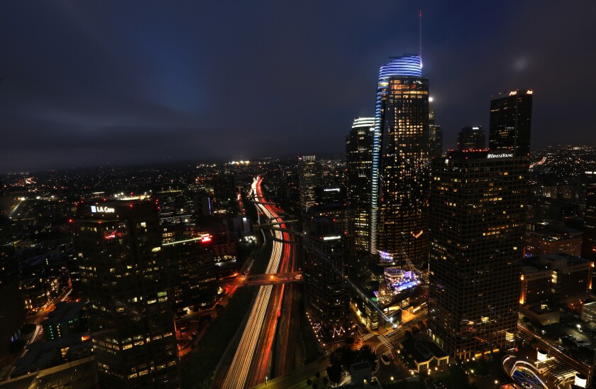 The Wilshire Grand Center, a 73-story skyscraper, dominates the L.A. skyline at dusk