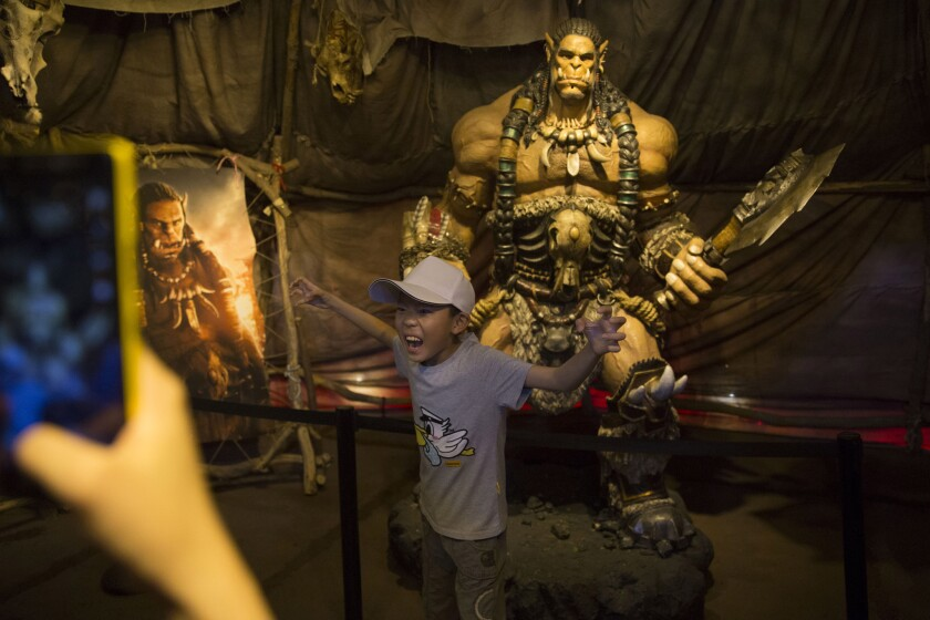 "A child poses infront of a statue of a character from the movie Warcraft in Beijing, China, Friday, June 10, 2016. ""Warcraft"" is a big-budget fantasy-action film with lots of large-scale, epic fight"
