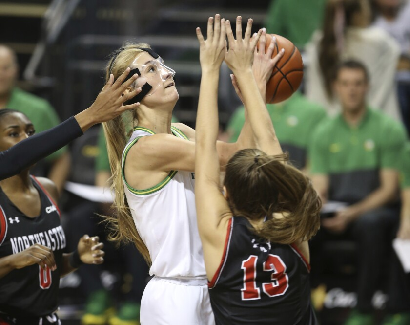 Oregon's Lydia Giomi, center, shoots between Northeastern's Mine Oriyomi, left, and Katie May during the fourth quarter of an NCAA college basketball game in Eugene, Ore., Monday, Nov. 11, 2019. (AP Photo/Chris Pietsch)