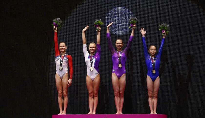 Four gold medal winners Madison Kocian of the U.S., from left, Russia's Daria Spiridonova, Russia's Viktoriia Komova and China's Fan Yilin celebrate on the podium after their uneven bars exercises at the women's apparatus final competition at the World Artistic Gymnastics championships at the SSE H