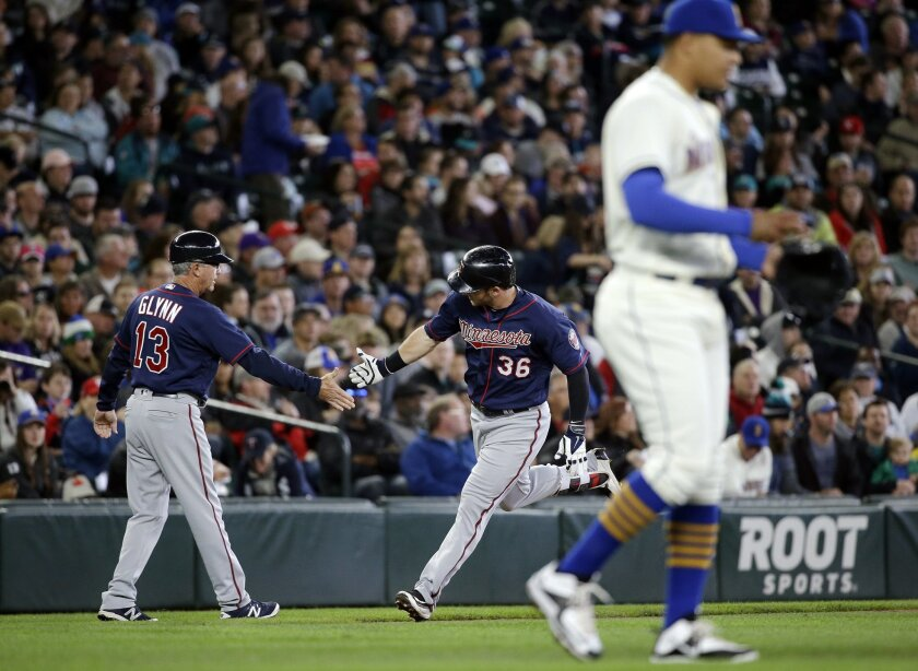 Seattle Mariners starting pitcher Taijuan Walker, right, returns to the mound as Minnesota Twins' Robbie Grossman (36) is congratulated by third base coach Gene Glynn on Grossman's home run in the second inning of a baseball game Sunday, May 29, 2016, in Seattle. (AP Photo/Elaine Thompson)