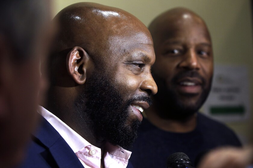 Entrepreneurs Kevin Hart, of Randolph, Mass., left, and Kobie Evans, of Boston, right, speak to reporters after attending a meeting of the Massachusetts Cannabis Control Commission, Thursday, Feb. 6, 2020, in Worcester, Mass. The commission voted in favor of licenses for a number of cannabis shops, including Pure Oasis, a soon to open pot shop in Boston's Dorchester neighborhood by Evans and Hart. (AP Photo/Steven Senne)