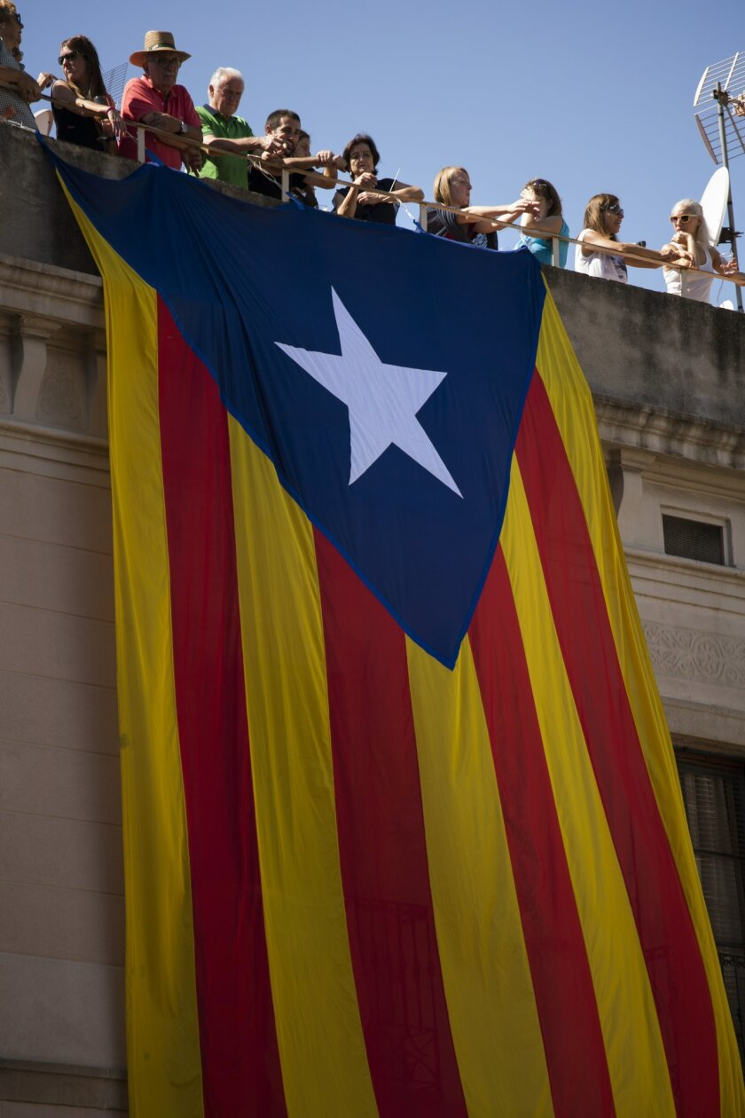 """In this Sunday, Sept. 20, 2015 photo, an """"estelada"""" or pro independence flag hangs on a building as people look at human towers or """"Castellers"""" in San Jaime square in Barcelona, Spain. Catalans vote Sunday in regional parliamentary elections that the breakaway camp hopes will give them a mandate to put their region on a path toward independence _ a goal the Madrid central government says would be illegal. (AP Photo/Emilio Morenatti)"""