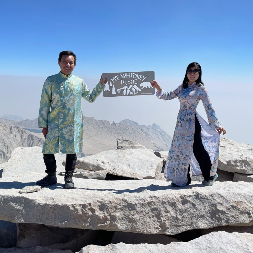 A man and woman, in traditional Vietnamese dress, hold a sign on Mt. Whitney.
