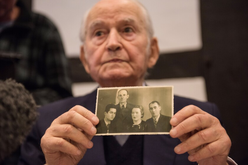 Leon Schwarzbaum, sobreviviente del campo de concentración de Auschwitz, muestra una vieja fotografía en la que aparece él (izquierda), junto a su tío y sus padres, que fallecieron todos en Auschwitz, durante una rueda de prensa en Detmold, Alemania.(Bernd Thissen/dpa via AP)