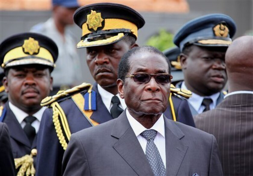 """Zimbabwe President Robert Mugabe arrives for the burial of a prominent member of his party, Misheck Chando, in Harare, Saturday, Oct. 31, 2009. Mugabe says he is committed to working with his estranged prime minister despite his assessment that the former opposition leader is """"not mentally stable"""" for boycotting the coalition government. (AP Photo/Tsvangirayi Mukwazhi)"""