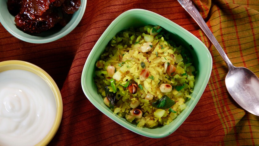 Kanda batata poha (pounded rice with onion and potatoes) served with yogurt.
