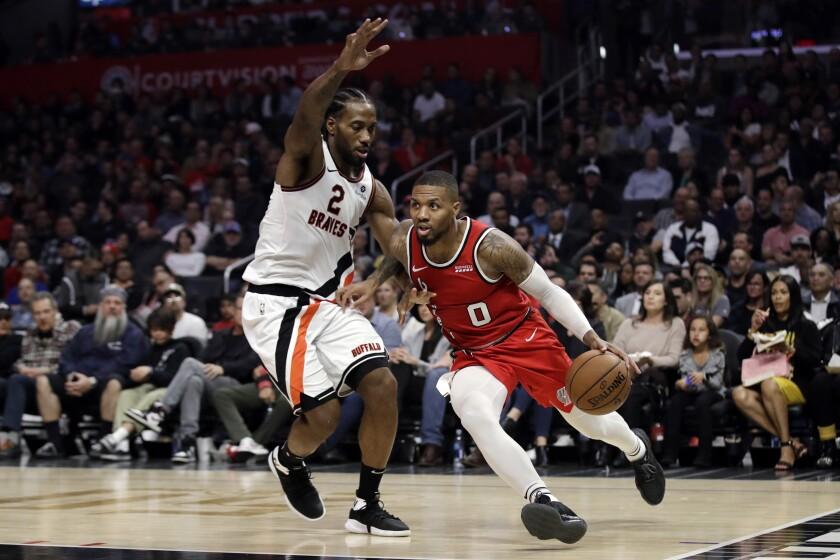 Portland Trail Blazers' Damian Lillard (0) dribbles next to Los Angeles Clippers' Kawhi Leonard (2) during the first half of an NBA basketball game Thursday, Nov. 7, 2019, in Los Angeles. (AP Photo/Marcio Jose Sanchez)