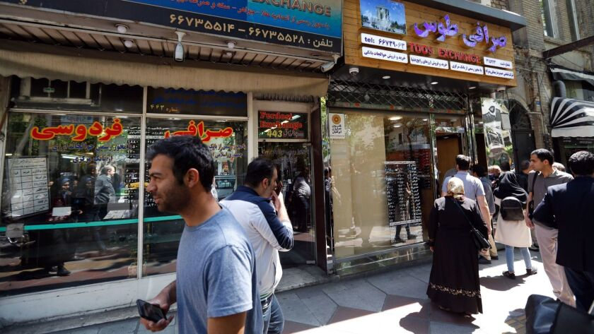 Iranians check the currency rate around a money exchange shop in Tehran.