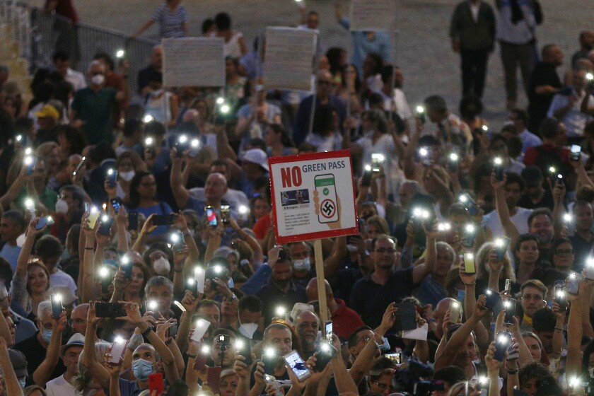 """FILE - In this Wednesday, July 28, 2021 file photo, people stage a protest against the COVID-19 vaccination pass in Rome. Shouts of """"liberty"""" have echoed through Italian and French streets and squares as thousands show their opposition to plans to require vaccination cards to continue normal social activities, like dining indoors at restaurants, visiting museums or cheering home teams in stadiums. (Cecilia Fabiano/LaPresse via AP)"""