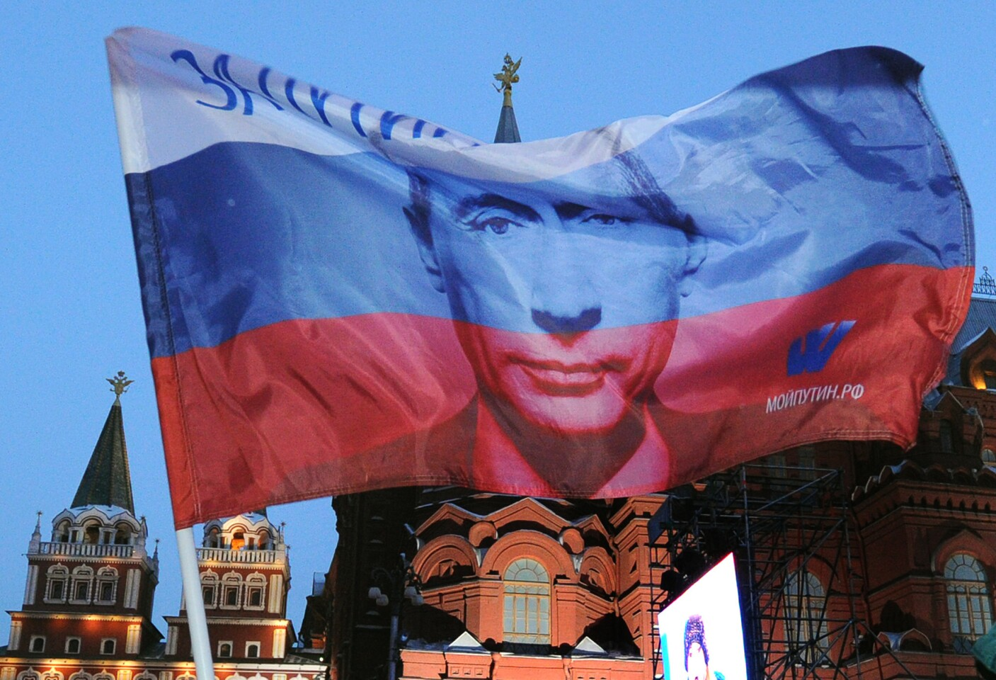 A Russian flag featuring Prime Minister Vladimir Putin flies above his supporters at a square just outside the Kremlin in Moscow as they celebrate Putin's election on March 5, 2012. Putin regained the presidency after four years as prime minister.