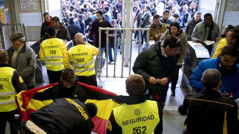 Security personnel frisk supporters before the Spanish league game between Real Madrid and Barcelona at the Santiago Bernabeu Stadium on Saturday.