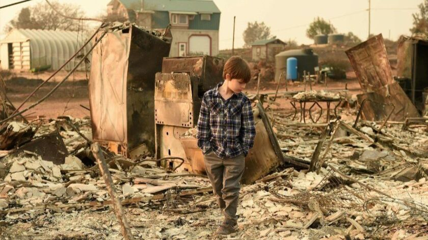 Jacob Saylors, 11, walks through the burned remains of his home in Paradise, Calif.