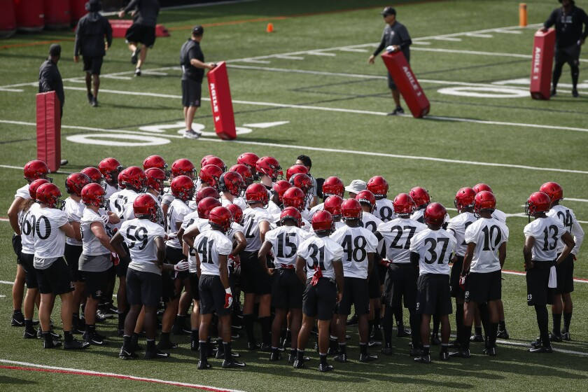 The defensive players huddle up around head coach Rocky Long before the start of drills at SDSU's first team practice.