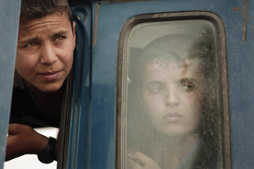 Two boys look out of a truck in a convoy carrying families fleeing Islamic State-held Hit, Iraq, at a checkpoint on the western edge of Ramadi, Iraq. Much of Iraq's north and west fell to the Islamic State group in the summer of 2014, but over the past year Iraq's military has slowly regained pockets of territory. While IS still controls a large swath of Iraq and neighboring Syria, the group has lost an estimated 40 percent of the territory it once held in Iraq, according to U.S.-led coalition officials. (AP Photo/Maya Alleruzzo)