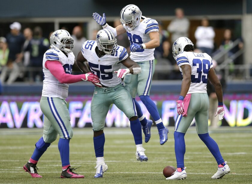 Dallas Cowboys middle linebacker Rolando McClain (55) celebrates with teammates after he intercepted a pass late in the second half of an NFL football game against the Seattle Seahawks, Sunday, Oct. 12, 2014, in Seattle. The Cowboys won 30-23. (AP Photo/Scott Eklund)