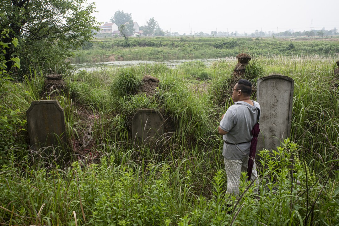 Pan Bangfeng looks at his ancestors' graves on what was once a plot of family farmland.