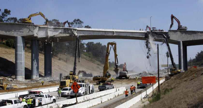"""FILE - In this July 16, 2011 file photo, pneumatic hammers from above and below continue the demolition of two lanes of Mulholland Drive bridge over Interstate 405 in Los Angeles as part of what was called Carmageddon, as it required the closure of the freeway for three days. """"Carmageddon II"""" will be coming to a major freeway near Los Angeles on the last weekend of April. The demolition of the Burbank Boulevard bridge over Interstate 5 in Burbank, Calif., a major link between Los Angeles and Northern California, will shut down the freeway for what authorities say will be 36 hours beginning at 3 p.m., Saturday, April 25, 2020. (AP Photo/Reed Saxon, File)"""