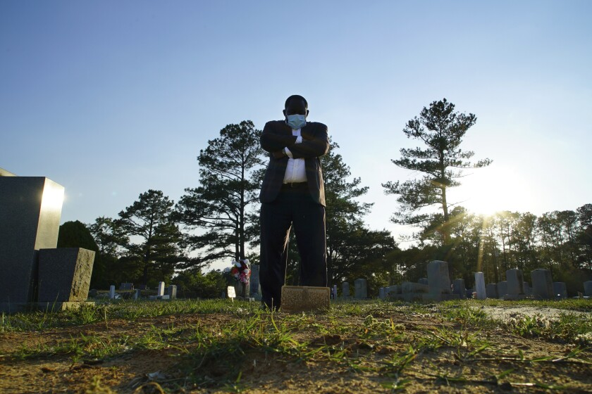 """Mortician Shawn Troy stands at the grave of his father, William Penn Troy Sr., at Hillcrest Cemetery outside Mullins, S.C., on Sunday, May 23, 2021. The elder Troy, who developed the cemetery, died of COVID-19 in August 2020, one of many Black funeral directors to succumb during the pandemic. """"I don't think I'll ever get over it,"""" he said. """"But I'll get through it."""" (AP Photo/Allen G. Breed)"""