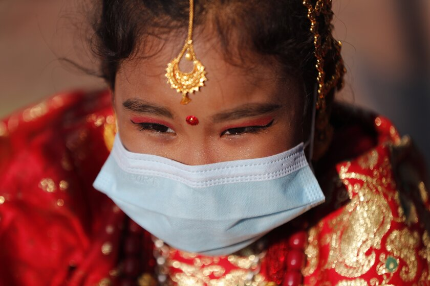 A young Newar girl waits for an Ihi ceremony in Kathmandu, Nepal, Friday, Dec. 4, 2020. Ihi is a two-day ceremony performed for girls who have not reached puberty and involves purification rituals and marriage rituals with the Bael (or wood apple). Newari girls are married thrice in their life, to the bael fruit and the sun before marrying a human. (AP Photo/Niranjan Shrestha)