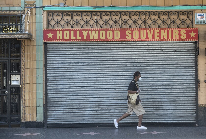 A pedestrian walks past a closed business on Hollywood Boulevard in Hollywood.