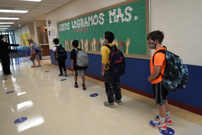 FILE - In this Sept. 3, 2020, file photo, students keep social distance as they walk to their classroom in Highwood, Ill., part of the North Shore school district. In response to a push for culturally responsive teaching that gained steam following last year's police killing of George Floyd, Republican lawmakers and governors have championed legislation to limit the teaching of material that explores how race and racism influence American politics, culture and law. The measures have become law in Tennessee, Idaho and Oklahoma and bills have been introduced in over a dozen other states. (AP Photo/Nam Y. Huh, File)