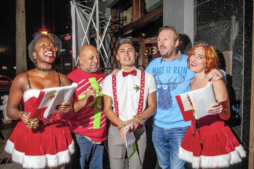 Carolers Alexis Udo-Udoma, Fermin Bello and Candace Small are joined by Incipio Chief Executive Andy Fathollahi and Stag Bar + Kitchen owner Mario Marovic outside the Newport Beach bar Thursday night.