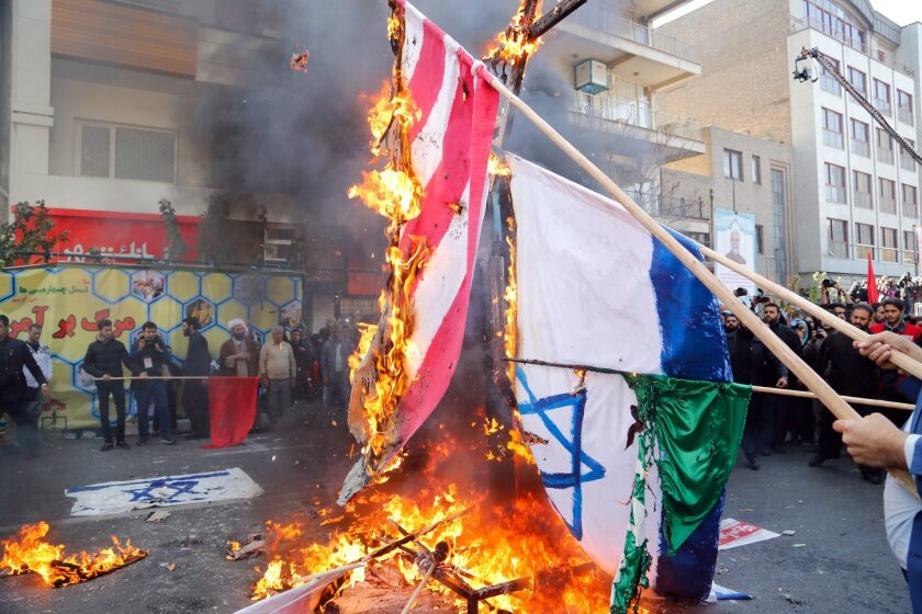 Iranian protesters burn U.S., Israeli and Saudi Arabian flags Nov. 3 as they mark the 37th anniversary of the U.S. Embassy takeover in front of the former embassy building in Tehran.