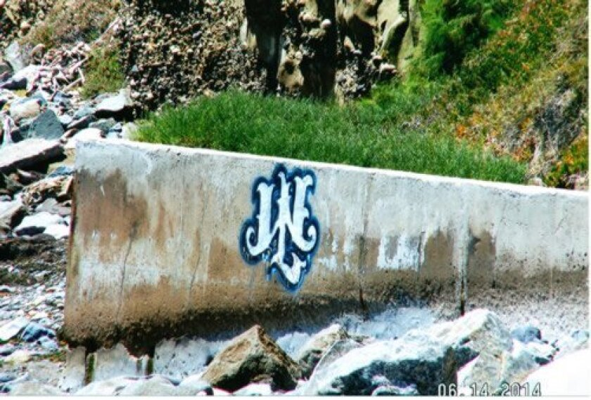 The seawall near a Bird Rock home is tagged with large letters. Courtesy